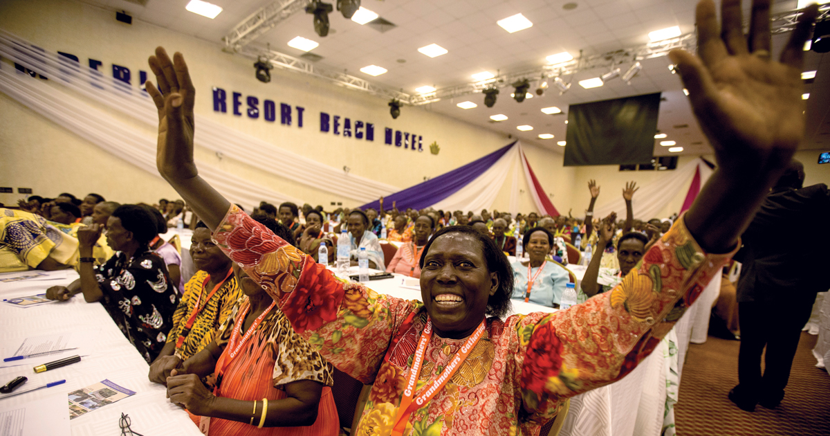 Smiling Ugandan woman with her arms outstretched with women seated in rows of tables behind her