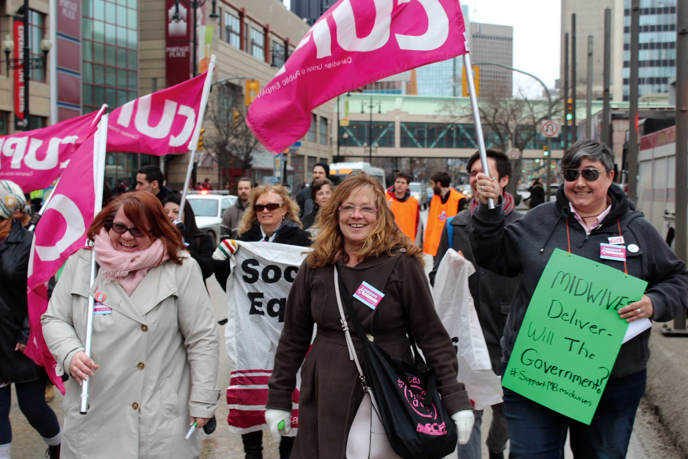 """Women march holding CUPE flags and a protest sign that says """"Midwives deliver: will the government?"""""""
