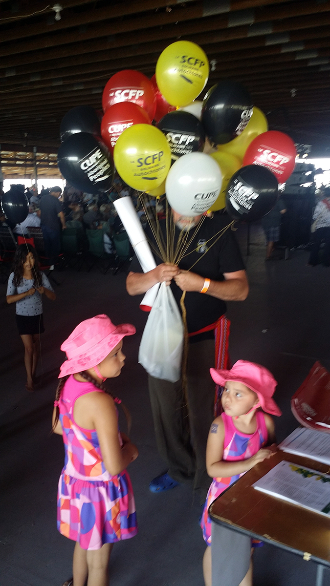 Man holding red, yellow, red and black balloons with two little girls in pink dresses and hats.