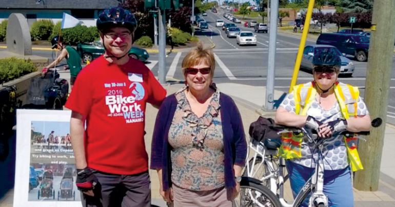 One man and two women stand with their bikes on a sunny day