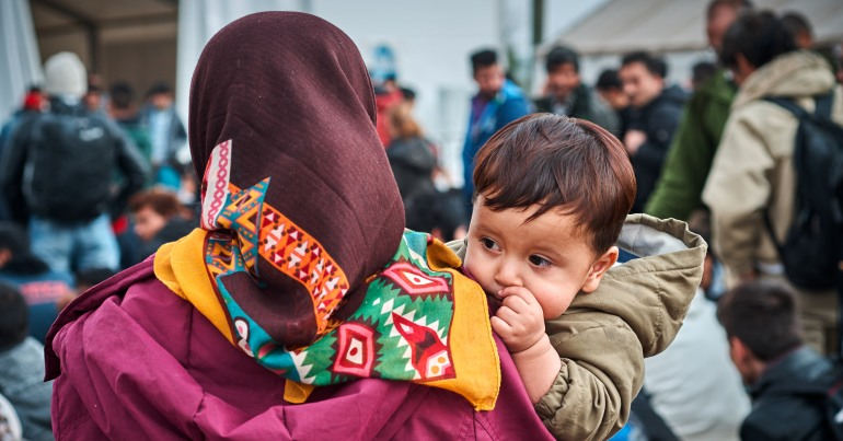 Woman with a colourful scarf holding a baby who looks over her shoulder at the camera.