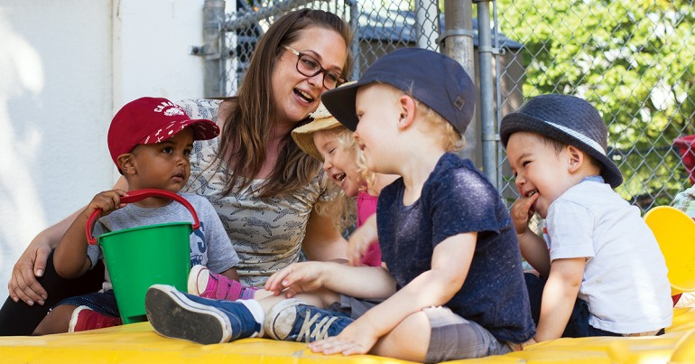 Four pre-school aged children laughing with a woman in glasses