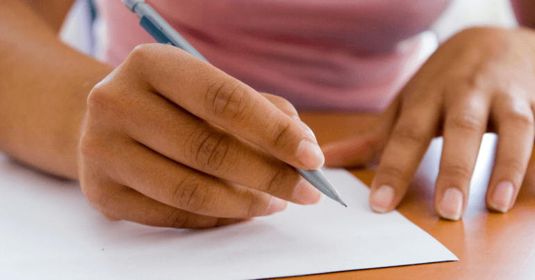 Hands holding a pencil poised above a piece of white paper
