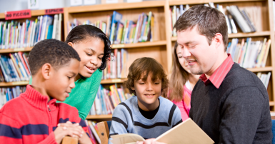 Man reading a book to four children with bookshelves in the background
