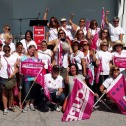Group of protesters with pink flags under an awning