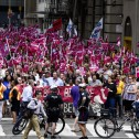Very large crowd with pink flags in a city street, police and bicycles in the foreground.