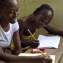Two Black women at a wooden desk writing with pencils on pads of paper