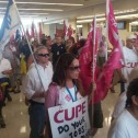 A crowd of mena and women with placards and flags march into a public building