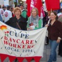 Three smiling white women holding a banner in a large crowd