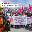 Group shot of workers holding CUPE signs supporting public libraries and big black dog