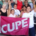 Group of women with raised fists holding a pink CUPE flag