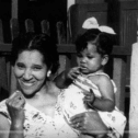 Black and white photo of a smiling black woman holding a black toddler girl in her arms, standing in front of a porch