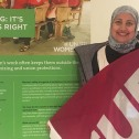 """A woman holding a bright pink CUPE flag standing beside poster that includes the text """"Organizing: It's a woman's right"""""""