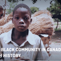 A young Black boy looks directly out of the frame, there are trees and a bundle of straw behind him